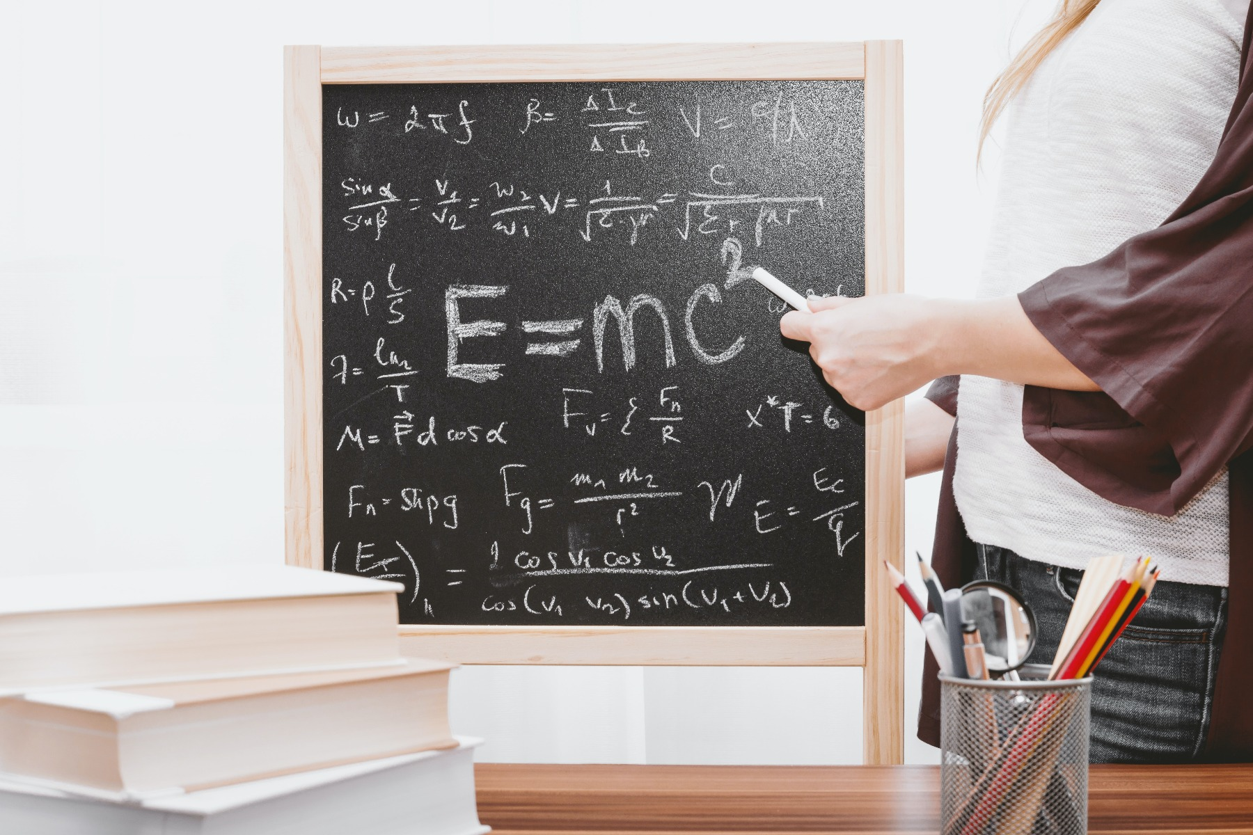 Woman pointing a piece of chalk to a chalkboard with math and an Einstein equation on it in a homeschool classroom.