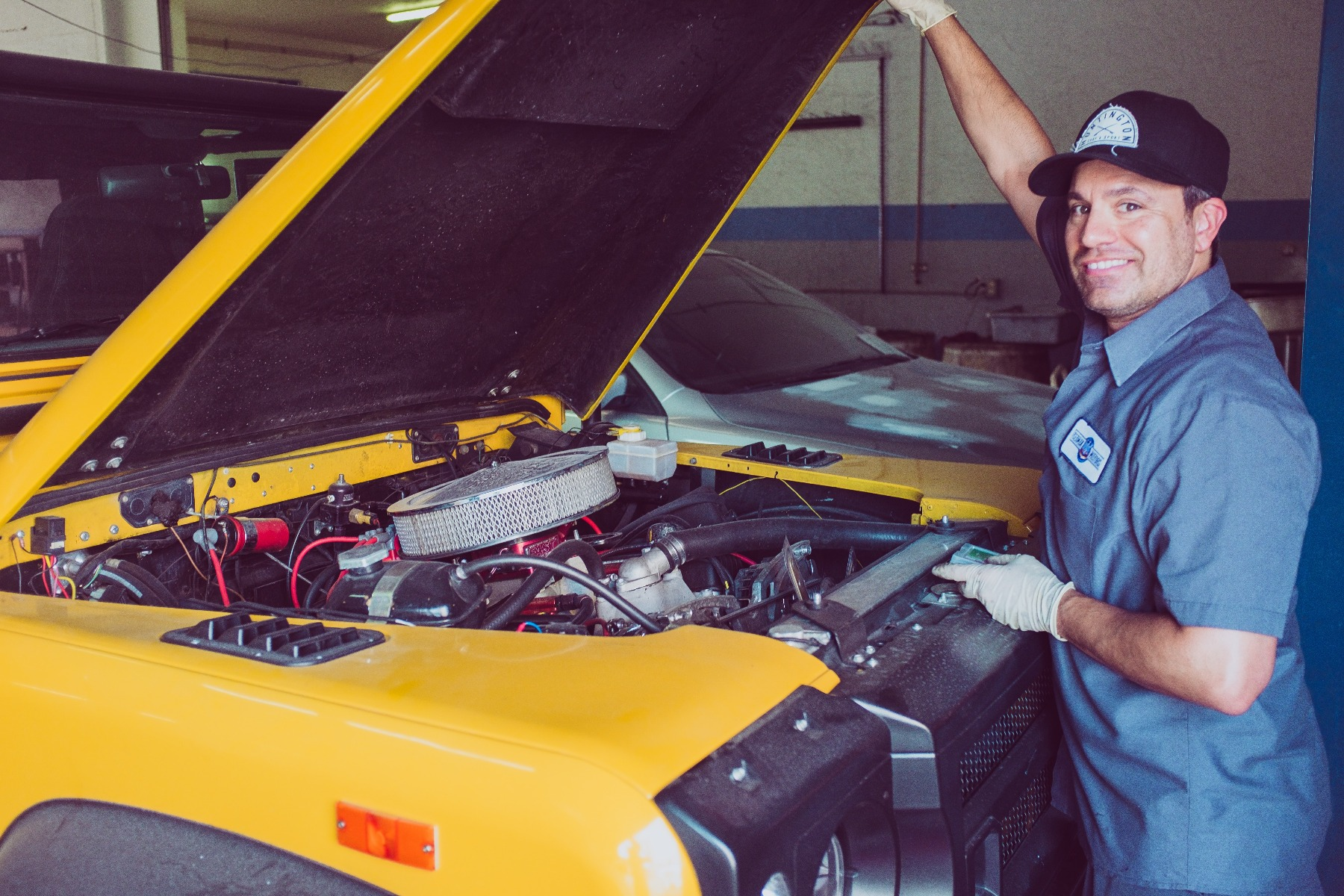 A mechanic works under the hood of a car using heat shrink tubing to combine wires.
