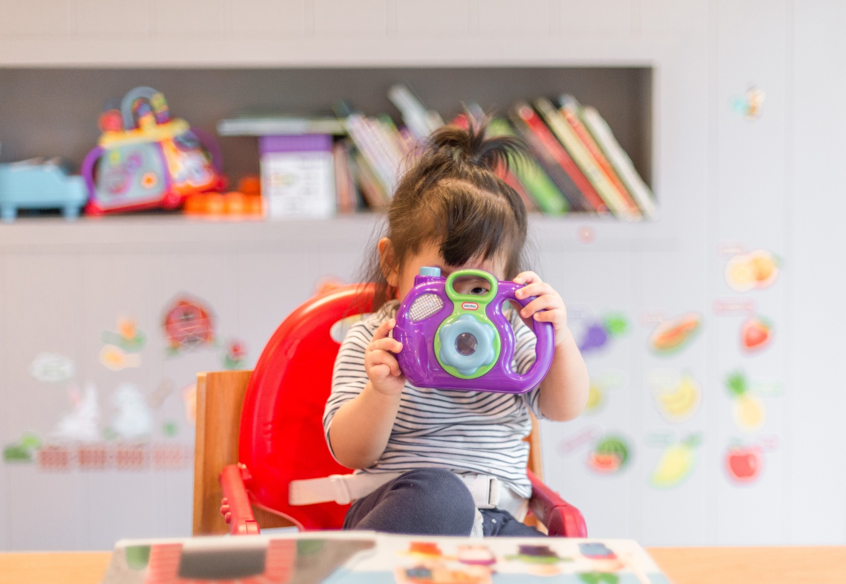 Little girl looks through toy camera lens while reading a picture book and sitting at a table in her homeschool classroom.