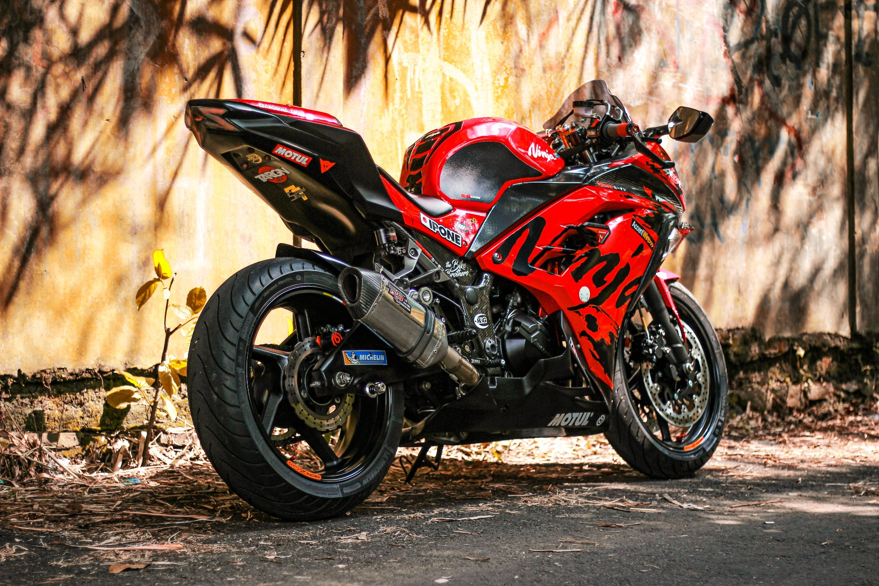 A red and black motorcycle is parked at the side of a building in the sunlight